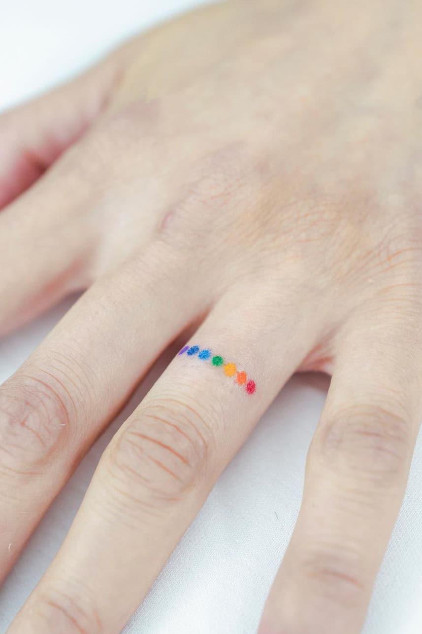 Rainbow dot tattoo on finger